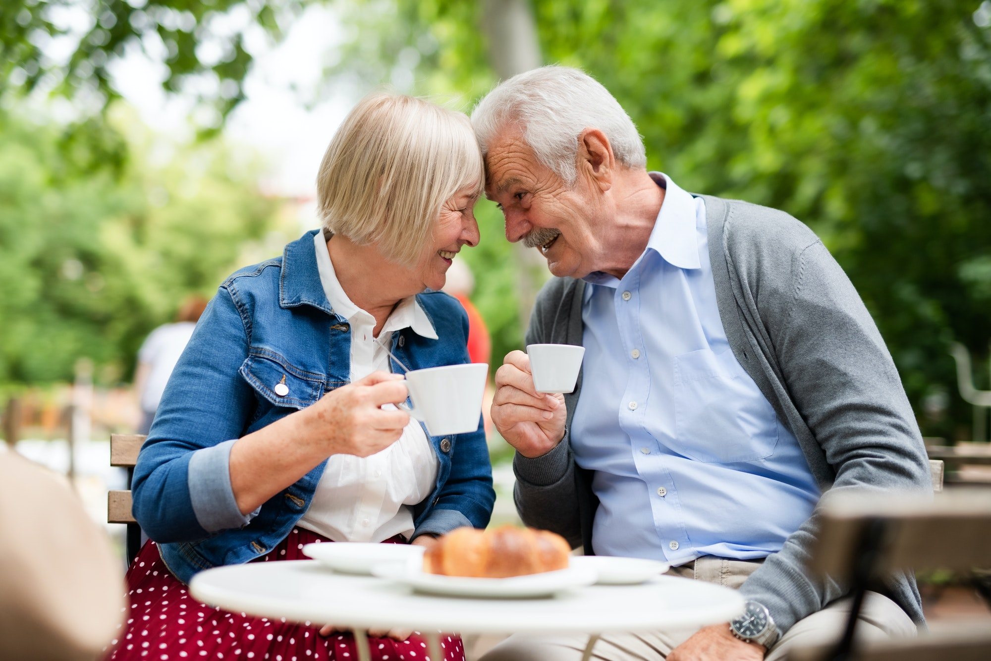 Happy senior couple in love sitting outdoors in cafe, having fun