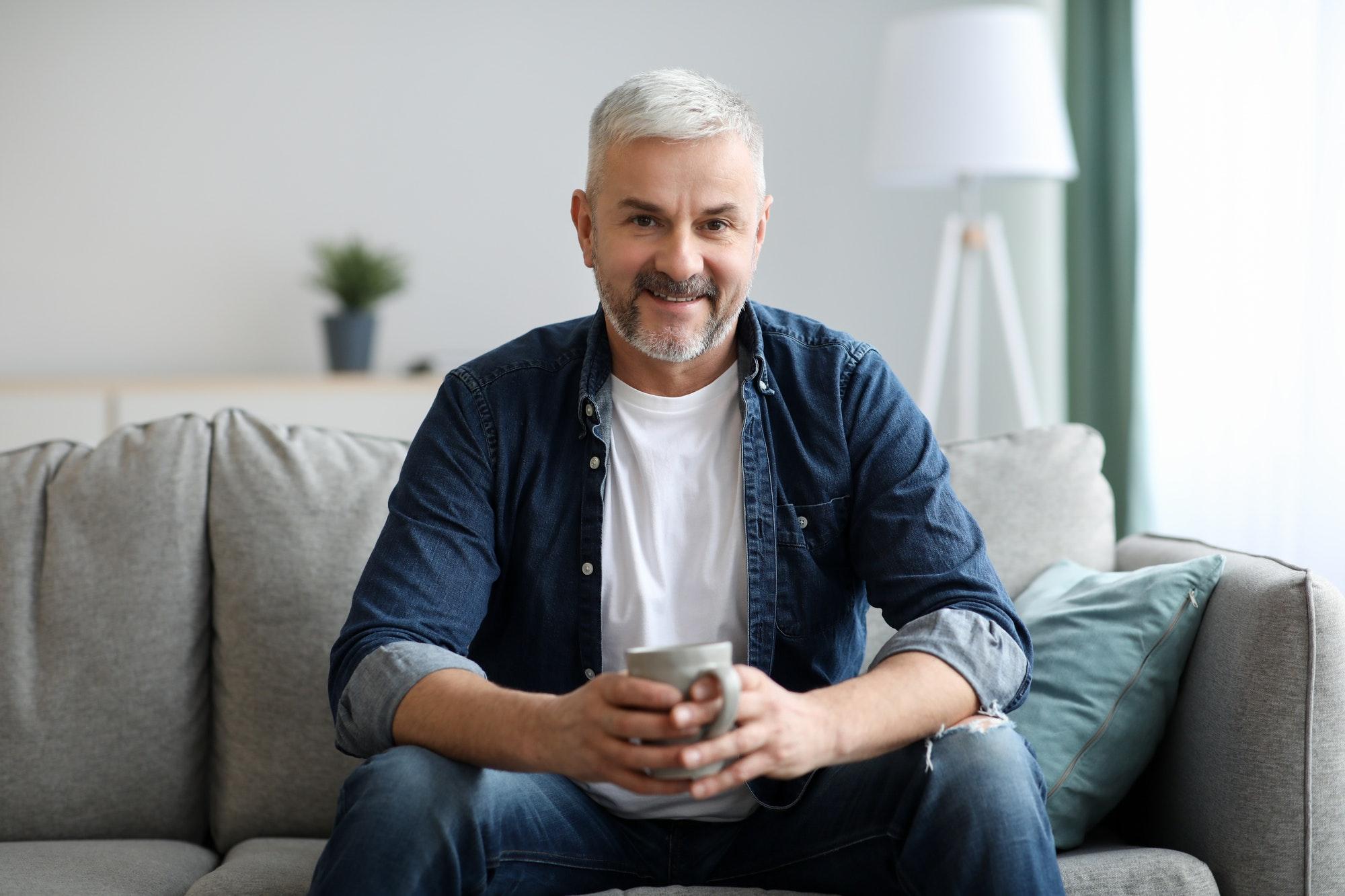 Cheerful senior man with mug of coffee